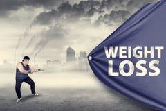 Uomo grasso che tira un'insegna di perdita di peso Immagine Stock