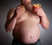 Uomo grasso con l'hamburger e le patatine fritte Fotografie Stock Libere da Diritti