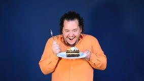 Uomo grasso divertente in camicia arancio con un pezzo di dolce di cioccolato su un piatto stock footage