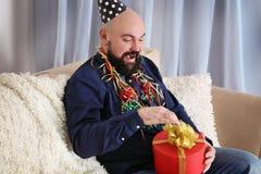 Uomo grasso divertente con regalo di compleanno che si siede sul sofà fotografia stock libera da diritti