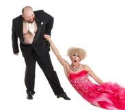 Uomo grasso eccentrico che trascina una donna dalla mano che si trova sul pavimento immagini stock