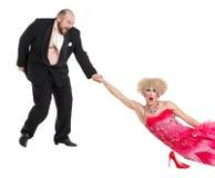 Uomo grasso eccentrico che trascina una donna dalla mano che si trova sul pavimento Immagine Stock