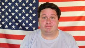 Uomo grasso, pulente il sudore con un fazzoletto sui precedenti di una bandiera di U.S.A. archivi video
