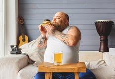 Uomo grasso spensierato che gode dell'odore dell'hamburger Fotografie Stock Libere da Diritti