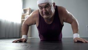 Uomo grassottello motivato nel suo 50s che fa flessione con grande sforzo, addestramento domestico Fotografie Stock