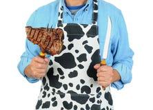 Uomo in grembiule con bistecca sulla forcella Fotografia Stock