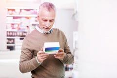 Uomo grigio-dai capelli non decisivo che legge i dettagli su un farmaco fotografia stock libera da diritti