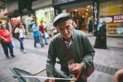 uomo grigio dei capelli che vende i dolci sulla via e che esamina macchina fotografica Fotografie Stock Libere da Diritti