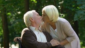 Uomo handicappato anziano che abbraccia insieme e che bacia la sua bella moglie, passatempo stock footage