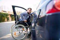 Uomo handicappato che tenta di ottenere nell'automobile fotografie stock