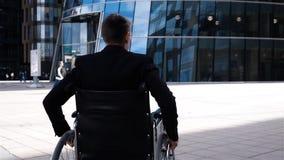 Uomo handicappato nel movimento della sedia a rotelle vicino al centro moderno di affari stock footage