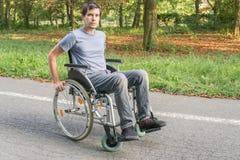Uomo handicappato o disabile dei giovani sulla sedia a rotelle fotografia stock libera da diritti