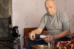 Uomo handicappato senior che prende la sua pressione sanguigna Fotografie Stock