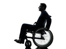 Uomo handicappato serio di vista laterale nella siluetta della sedia a rotelle Fotografia Stock Libera da Diritti