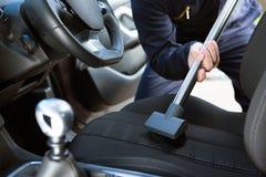 Uomo Hoovering Seat dell'automobile durante la pulizia dell'automobile Immagine Stock