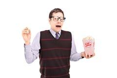 Uomo impaurito che tiene un contenitore di popcorn Immagini Stock