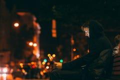 Uomo incappucciato che chiacchiera con il computer portatile nella notte Fotografie Stock Libere da Diritti