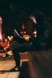 Uomo incappucciato che si siede sul banco con il computer portatile Fotografie Stock Libere da Diritti