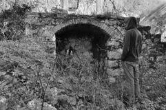 Uomo incappucciato vicino all'incavo incurvato di rovina rurale fotografia stock libera da diritti