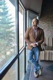 Uomo indiano allegro ed alla moda che sta vicino alla finestra Fotografia Stock Libera da Diritti