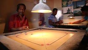 Uomo indiano che gioca il carrom indiano tradizionale uno del gioco da tavolo su uno archivi video