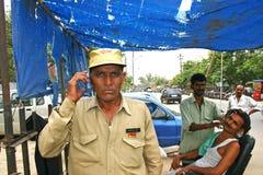 Uomo indiano che parla sul suo telefono cellulare ad un negozio di barbiere del bordo della strada fotografia stock