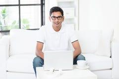 Uomo indiano che per mezzo del computer a casa Fotografie Stock Libere da Diritti