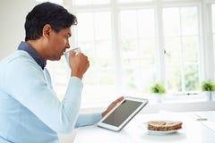 Uomo indiano che per mezzo della compressa di Digital mentre mangiando prima colazione Fotografie Stock