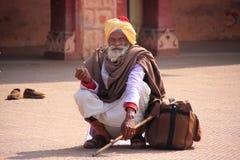 Uomo indiano che si siede alla stazione ferroviaria, Sawai Madhopur, India Fotografia Stock