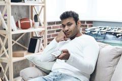 Uomo indiano che si siede sul sofà con telecomando immagini stock libere da diritti