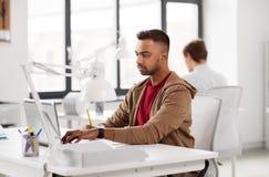Uomo indiano con il computer portatile all'ufficio Fotografia Stock