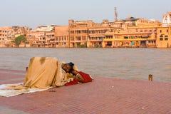 Uomo indiano povero che dorme all'aperto Haridwar Ganges Fotografia Stock