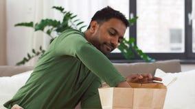 Uomo indiano sorridente che disimballa alimento asportabile a casa video d archivio