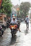 Uomo indonesiano che guida una motocicletta sotto la pioggia, Ubud, Bali Immagini Stock Libere da Diritti