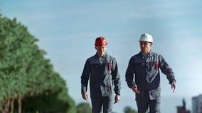 Uomo industriale due nella possibilit? remota media all'aperto di camminata di conversazione degli abiti da lavoro e del casco stock footage