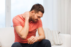 Uomo infelice che soffre dal dolore al collo a casa Immagine Stock Libera da Diritti