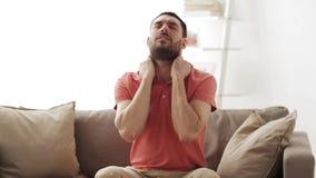 Uomo infelice che soffre dal dolore al collo a casa stock footage