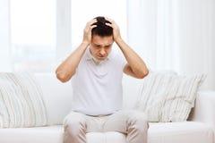Uomo infelice che soffre dal dolore capo a casa Immagine Stock Libera da Diritti