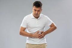 Uomo infelice che soffre dal dolore di stomaco Fotografie Stock Libere da Diritti