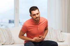 Uomo infelice che soffre dal dolore di stomaco a casa Fotografie Stock