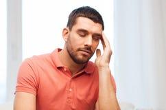 Uomo infelice che soffre dall'emicrania a casa immagini stock libere da diritti