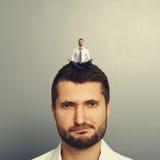 Uomo insoddisfatto con il piccolo uomo sulla testa fotografia stock libera da diritti