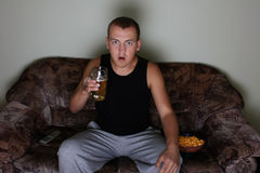 Uomo interessato che guarda TV con birra e le patatine fritte Immagini Stock Libere da Diritti
