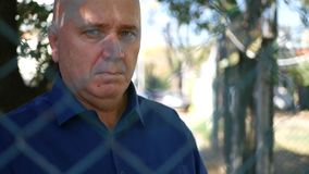 Uomo interessato che sembra diretto triste un recinto metallico da un'area di protezione video d archivio