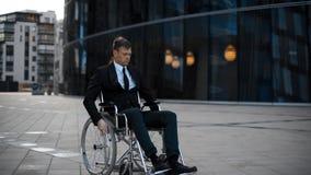Uomo invalido bello che si siede arrivando a fiumi sedia a rotelle e guardando deprimente stock footage