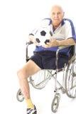 Uomo invalido in sedia a rotelle con la sfera di calcio Fotografie Stock Libere da Diritti