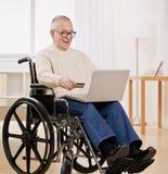 Uomo invalido in sedia a rotelle usando la carta di credito Fotografia Stock Libera da Diritti