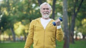 Uomo invecchiato bello che fa gli esercizi di braccio con le teste di legno in parco, attività di svago archivi video