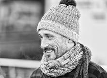 Uomo invecchiato in cappello e sciarpa di inverno Ritratto del tipo sorridente sulla via Tipo in sciarpa e cappello tricottati fotografia stock libera da diritti