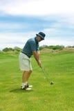 Uomo invecchiato centrale che gioca golf. Immagine Stock